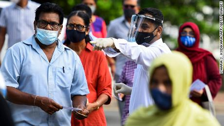 Sri Lankan voters cast their ballots with masks and face shields as parliamentary elections went on during the coronavirus pandemic.
