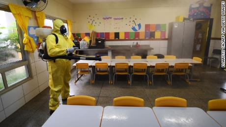 A Federal District employee disinfects a public school as a countermeasure against the spread of coronavirus in Brasilia, August 5, 2020.