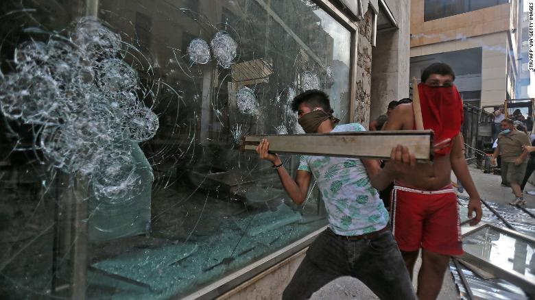 A Lebanese demonstrator breaks a shop window during clashes with security forces in Beirut.