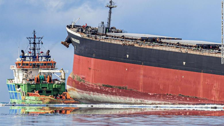 Workers look from a ship towards the vessel MV Wakashio that ran aground.