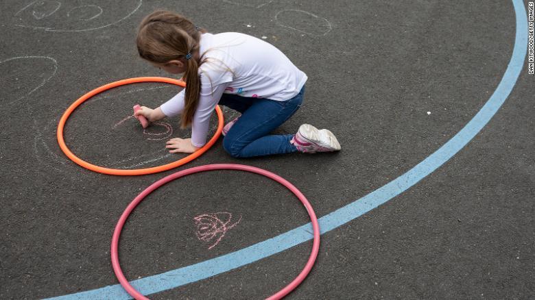 Copiii mențin măsuri de distanțare socială la o școală din Londra în iunie.