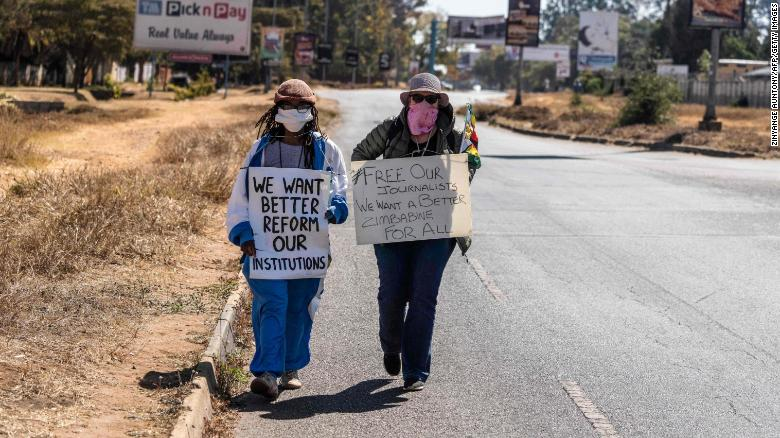 Zimbabwean novelist Tsitsi Dangarembga (L) and a colleague Julie Barnes hold placards during an anti-corruption protest march on July 31, 2020 in Harare.