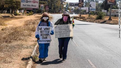 TOPSHOT - Zimbabwean novelist Tsitsi Dangarembga (L) and a colleague Julie Barnes hold placards during an anti-corruption protest march along Borrowdale road, on July 31, 2020 in Harare. - Police in Zimbabwe arrested on July 31, 2020 internationally-aclaimed novelist Tsitsi Dangarembga as they enforced a ban on protests coinciding with the anniversary of President Emmerson Mnangagwa's election. Dangarembga, 61, was bundled into a police truck as she demonstrated in the upmarket Harare suburb of Borrowdale alongside another protester. (Photo by ZINYANGE AUNTONY / AFP) (Photo by ZINYANGE AUNTONY/AFP via Getty Images)