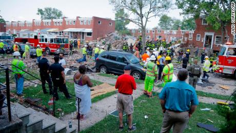 People gather outside an explosion site in Baltimore on Monday.