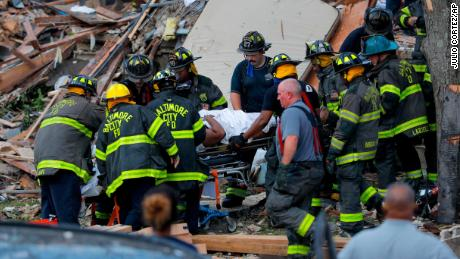 Firefighters carry someone from the debris in Baltimore on Monday.