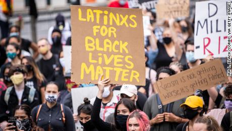 "A protester holds a sign that reads, ""LATiNXS FOR BLACK LiVES MATTER"" in New York on June 2."