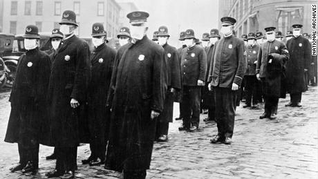 Police officers in Seattle wearing masks made by the Red Cross during the influenza epidemic in December 1918.