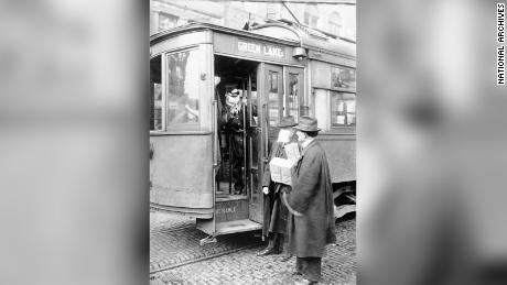 A street car conductor in Seattle not allowing passengers aboard without a mask in 1918.