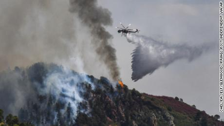 Fire crews work to battle the Grizzy Creek Fire as it shoots down the ridge into No Name Canyon.