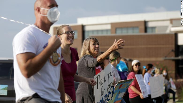 Supporters of the Cherokee County School District's decision to reopen schools cheer on faculty arriving to the district's headquarters in Canton, Georgia.