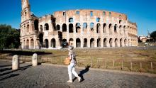 A woman walks in front of the Colosseum on July 10 in Rome, Italy.