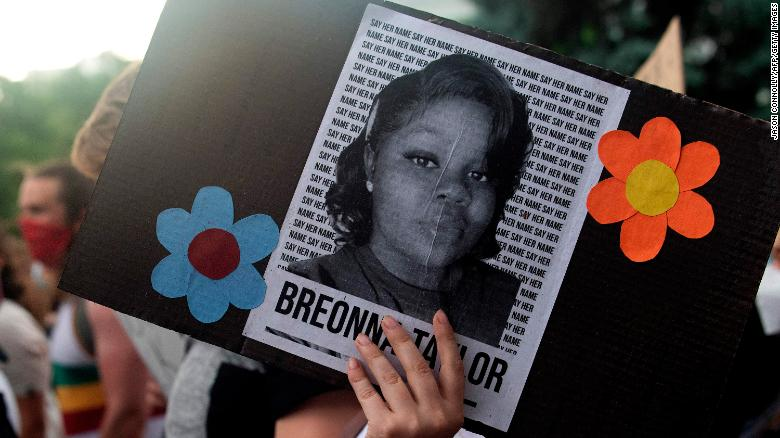 A demonstrator holds an image of Breonna Taylor during a protest in Denver last June.