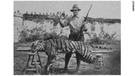 """Methodist minister Harry Caldwell, with a tiger he killed in Fujian. He wrote of the animal: """"I shot the animal with a .22-caliber high-power Savage rifle at close range, after the animal had charged me from a long distance. This is a bit of real missionary work I have greatly enjoyed, and incidentally have found most helpful in the preaching of the gospel."""