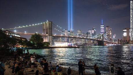 "People on the shore watch the ""Tribute in Light"" shining into the New York sky on September 11, 2019."