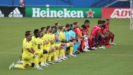 Players of FC Dallas (R) and Nashville SC kneel during the US national anthem before their game in Frisco, Texas.