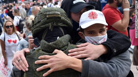 Protesters in Minsk embrace a Belarus law enforcement officer during a rally against President Alexander Lukashenko, who is accused of falsifying the polls in Sunday's election.