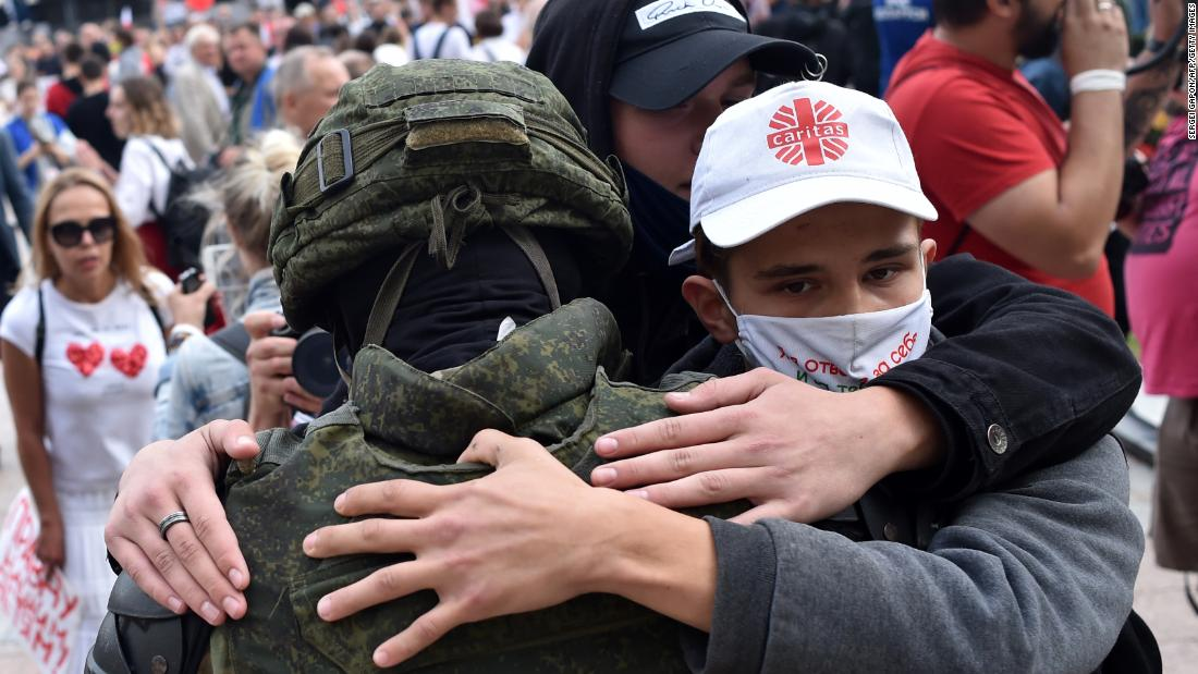 Belarus riot police drop shields and are embraced by anti-government protesters – CNN