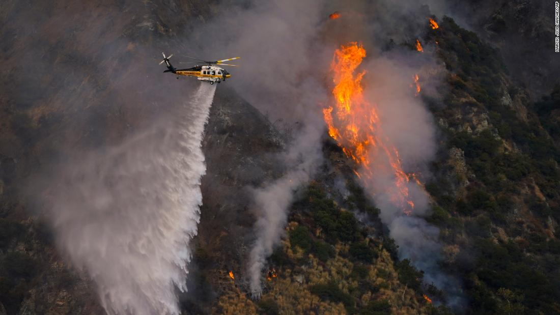 A helicopter makes a water drop over the Ranch2 Fire in Azusa, California, on Thursday, August 13.