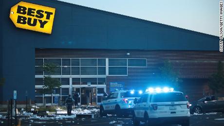 Los oficiales de policía inspeccionan una tienda Best Buy dañada el 10 de agosto de 2020 después de que el saqueo y el vandalismo generalizados se extendieran por partes de Chicago.