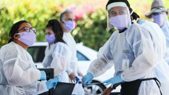 Healthcare workers, wearing personal protective equipment (PPE), facilitate tests at a drive-in coronavirus (COVID-19) testing center at M.T.O. Shahmaghsoudi School of Islamic Sufism on August 11, 2020 in Los Angeles, California. California reported 12,500 new cases after backlogged cases from a data glitch began appearing in the state's system. (Photo by Mario Tama/Getty Images)