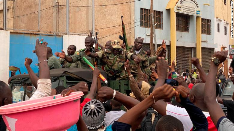 Malian soldiers are celebrated as they arrive at the Independence square in Bamako on August 18