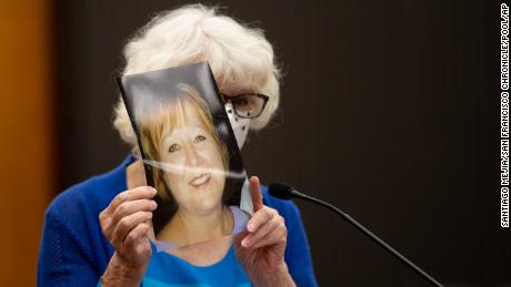 Dolly Kreis holds a photo of her daughter Debbie Strauss and shows it to Joseph James DeAngelo, known as the Golden State Killer, who did not look back, during the first day of victim impact statements.