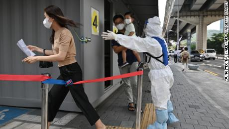 A health official wearing protective gear guides visitors at a Covid-19 coronavirus testing station in Seoul on August 18, 2020.