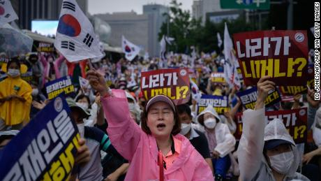 Members of conservative christian groups wave flags and shout slogans during an anti-government rally in the central Gwanghwamun area of Seoul on August 15, 2020.