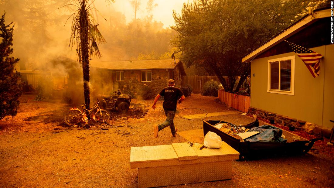 A resident runs into a home to save a dog while flames from the Hennessy Fire close in near Lake Berryessa on August 18.