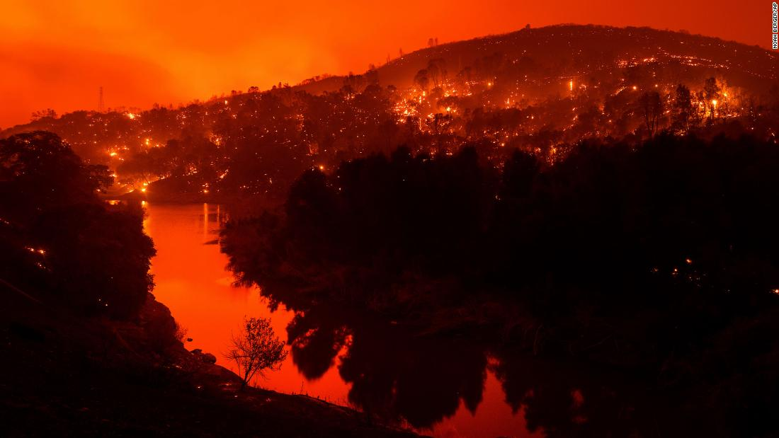 Embers burn along a hillside above Lake Berryessa as the LNU Lightning Complex fires tear through Napa County, California, on Tuesday, August 18. This image was taken with a long exposure.