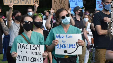 Medical workers hold signs during a rally, organized by a group named White Coats for Black Lives, on June 6 in New York.