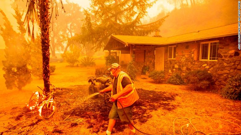 A resident hoses down a burning bicycle and tree as the Hennessey Fire approaches a home in Napa, California.