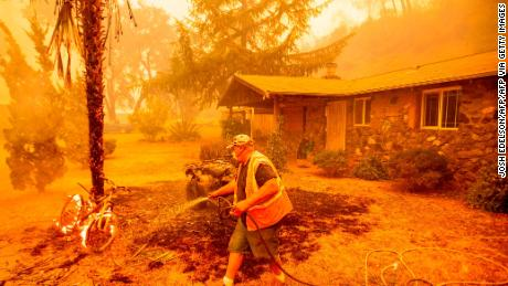 A resident hoses down a burning bicycle and tree as flames from the Hennessey Fire approach a property in Napa, California.