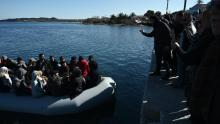 Migrants are seen on an inflatable boat as local residents prevent them from disembarking on the Greek island of Lesbos on March 1.