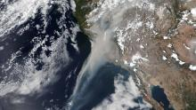 Smoke from the California wildfires is seen stretching some 600 miles off the coast in a NASA satellite image Wednesday.