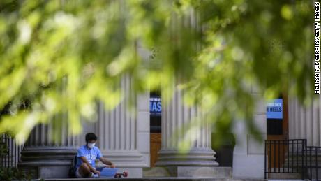 A student studies outside the closed Wilson Library on the campus of the University of North Carolina at Chapel Hill on August 18, 2020 in Chapel Hill, North Carolina. The school halted in-person classes and reverted back to online courses after a rise in the number of COVID-19 cases.