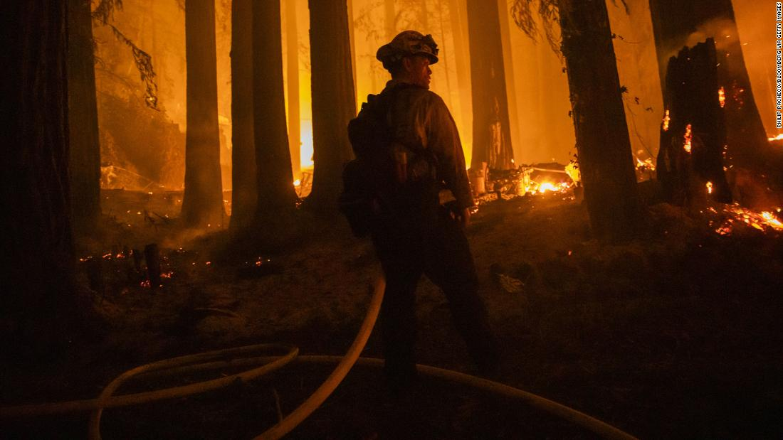 A firefighter battles flames in Santa Cruz County, California, on Thursday, August 20.