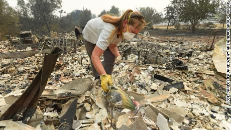 Sarah Hawkins finds a vase in the rubble after her home was destroyed by a fire in Vacaville, California.
