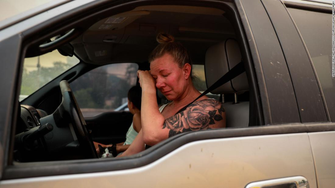 Gina Santos cries in her car after evacuating Vacaville on August 19.