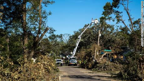 Tree branches pile up along the street as power line crews with Alliant Energy work to repair electrical lines on  Tuesday, August 18, 2020, in Cedar Rapids, Iowa.