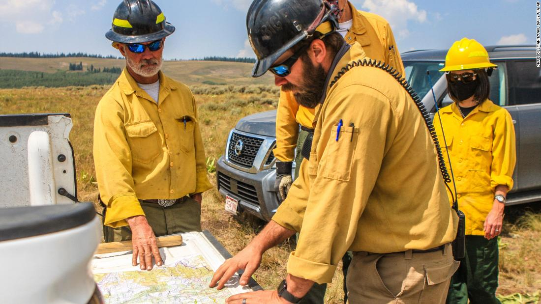 Members of the US Forest Service discuss their next moves to battle the Grizzly Creek Fire near Dotsero, Colorado, on August 21.