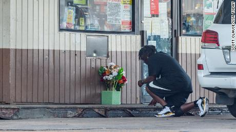 A man kneels to say a prayer outside convenience store on Evangeline Thruway where a man was shot and killed by Lafayette Police. Saturday, Aug. 22, 2020.