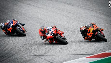 Oliveira (left) overtakes Espargaro (right) and Miller on the final corner for victory.