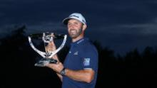 Johnson celebrates with the trophy after winning The Northern Trust.