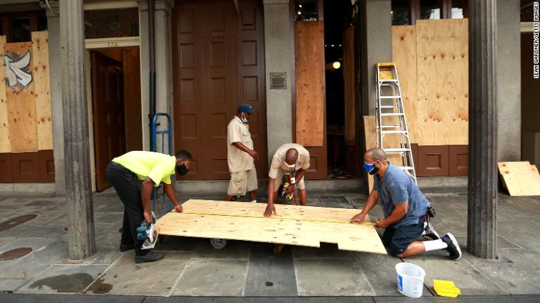 Workers board up windows in New Orleans' French Quarter before tropical storms Marco and Laura.