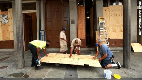 Workers board up windows in the French Quarter in anticipation of Hurricane Marco and Tropical storm Laura.