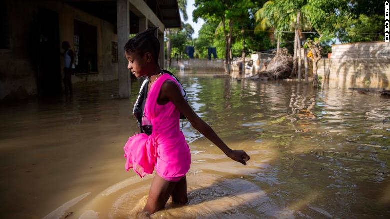 A girl wades toward her flooded home Monday after Tropical Storm Laura hit Port-au-Prince, Haiti.