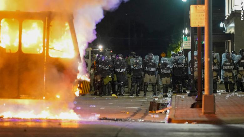 Police stand near a garbage truck ablaze during protests Monday in Kenosha.