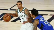 Bucks' George Hill (left) dribbles against the Orlando Magic in the NBA playoffs.