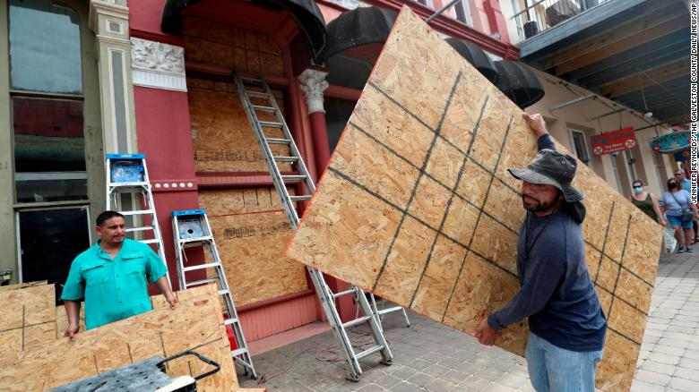 Cesar Reyes, right, carries a sheet of plywood to cut to size as he and Robert Aparicio, left, and Manuel Sepulveda, not pictured, install window coverings in Galveston on Monday.